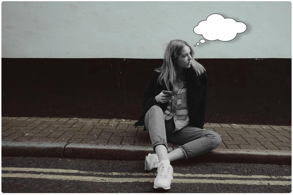 frau sitzt auf bordstein und wartet auf nachricht von ihrem freund