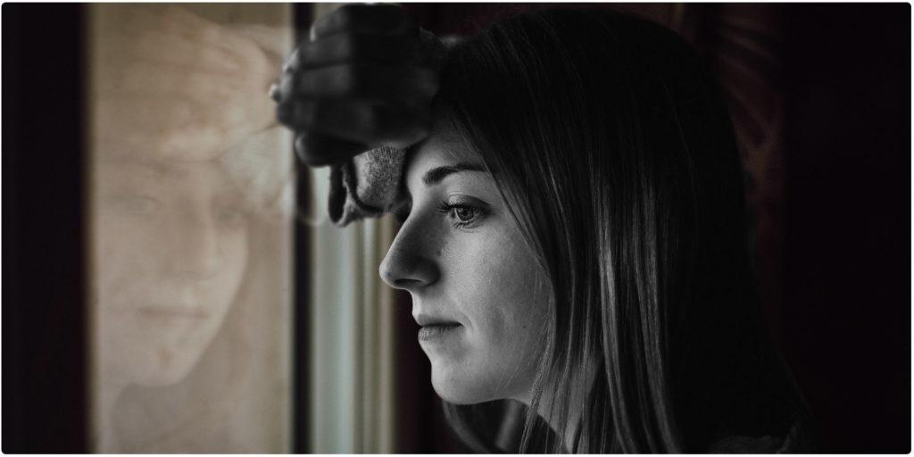 Funkstille nach Streit Frau steht am Fenster
