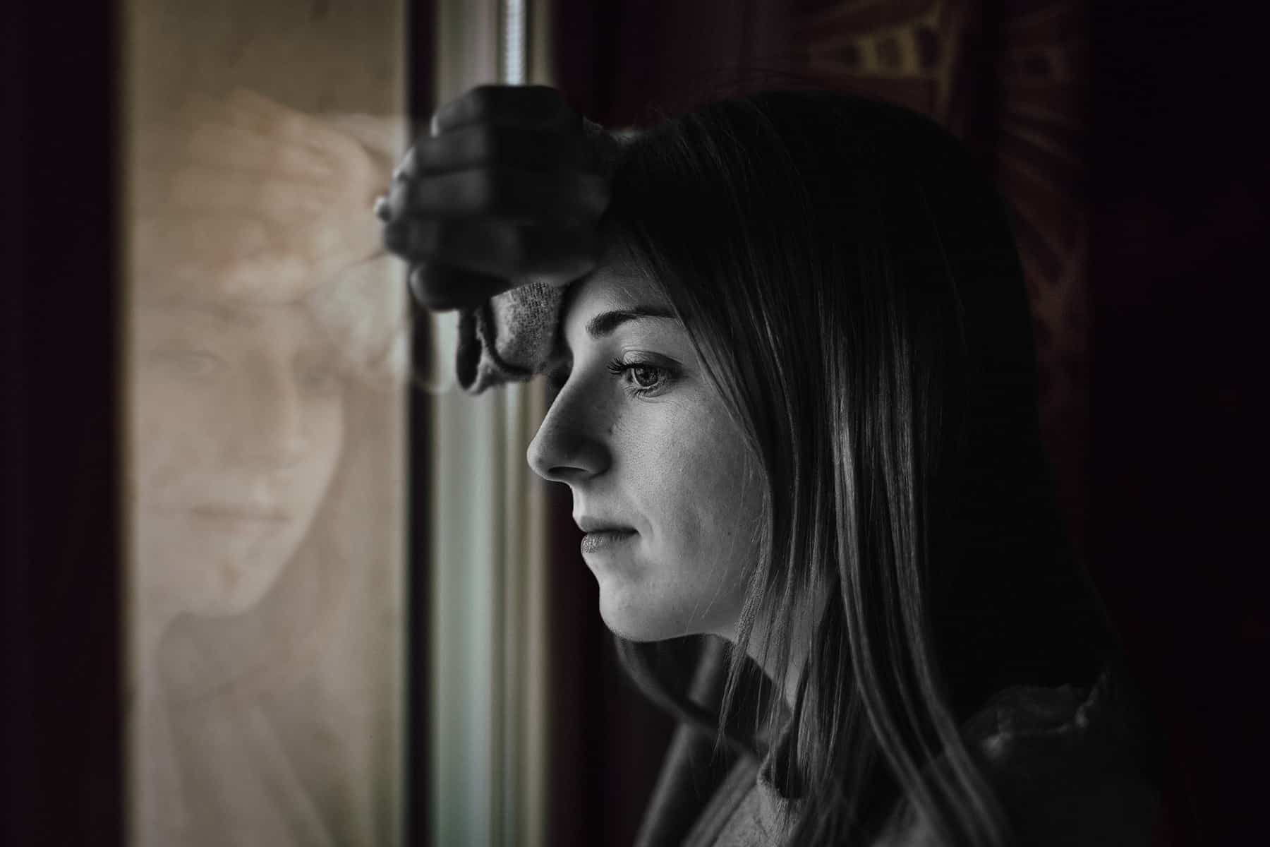 Frau steht am Fenster