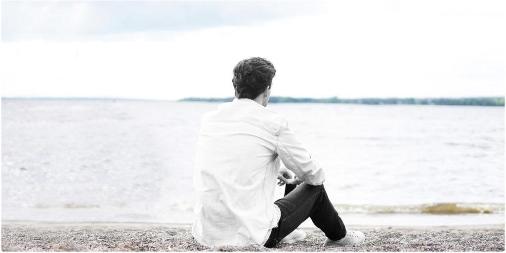 Mann sitzt alleine am Strand