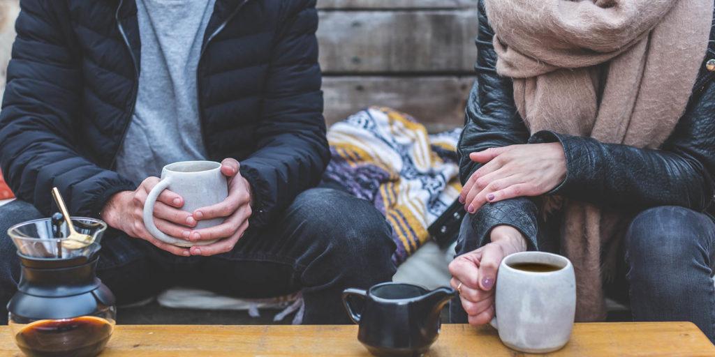 Mann und Frau unterhalten sich und trinken einen Kaffee
