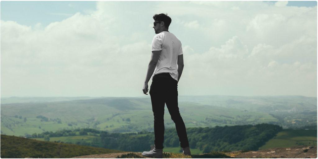 Selbstbewusster Mann steht auf einem Berg