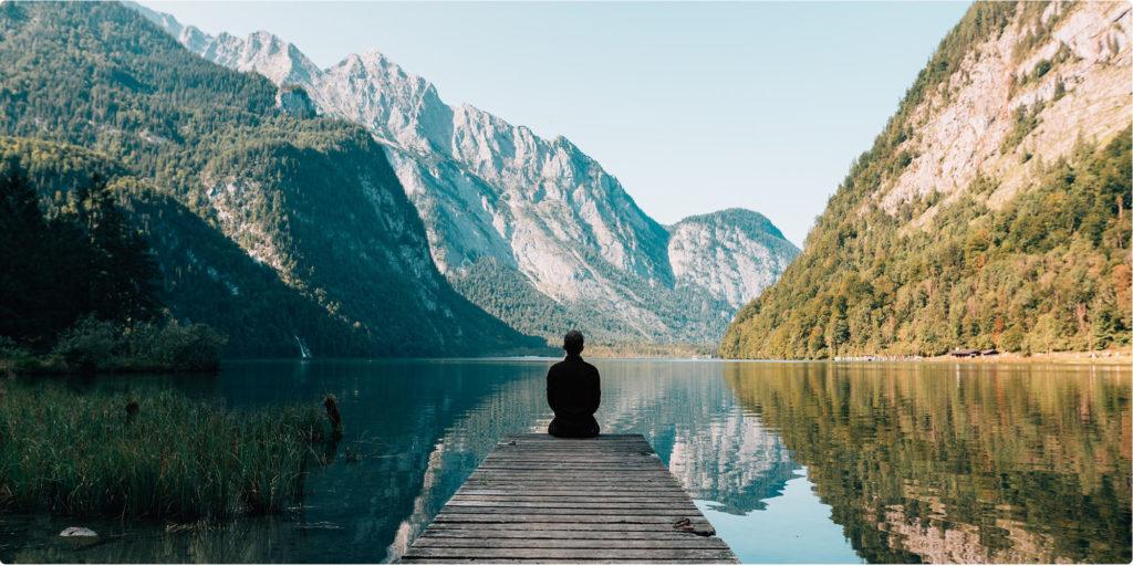 Mann sitzt alleine am See