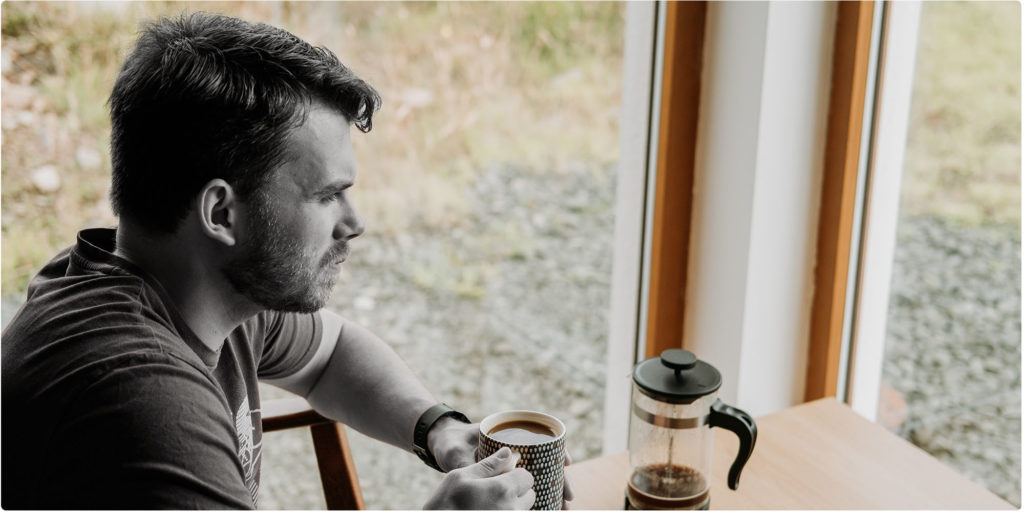 Mann trinkt Kaffee und schaut aus dem Fenster