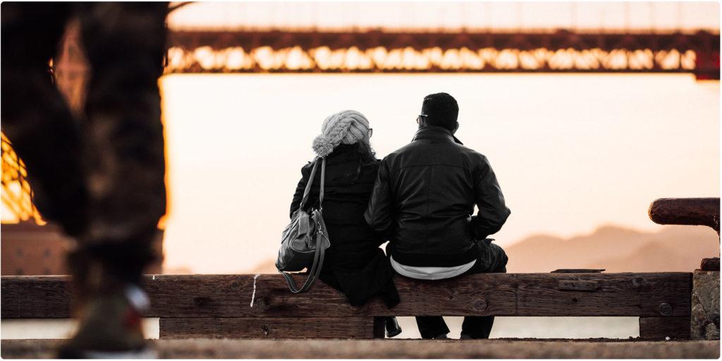 Mann und Frau unterhalten sich auf einer Parkbank