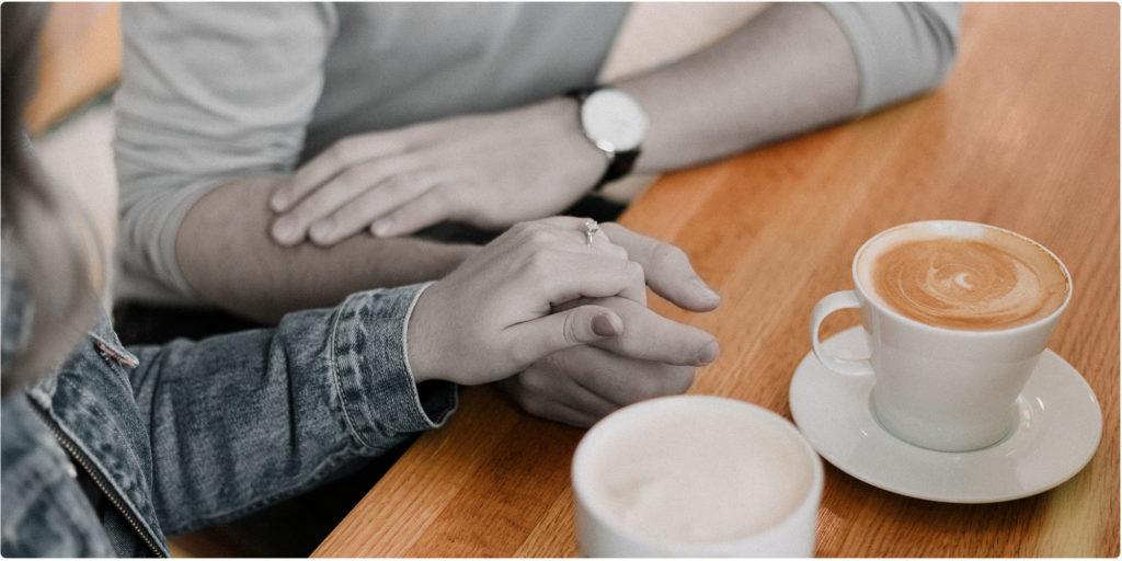 Paar unterhält sich am Tisch und trinkt Kaffee