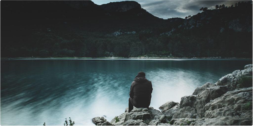 Mann sitzt an einem See