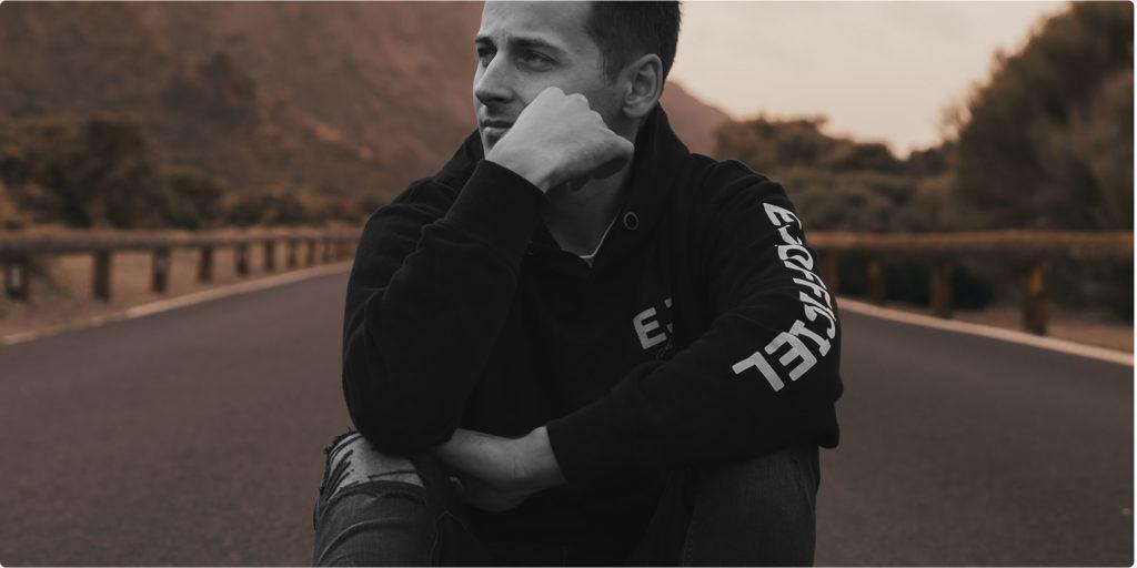 Mann sitzt auf der Straße und denkt nach