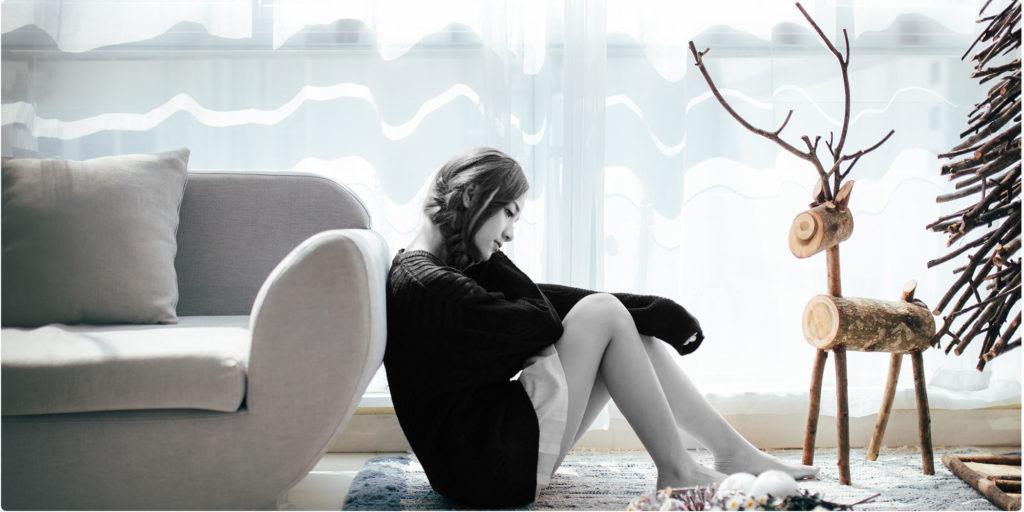 Frau sitzt auf dem Boden und denkt nach