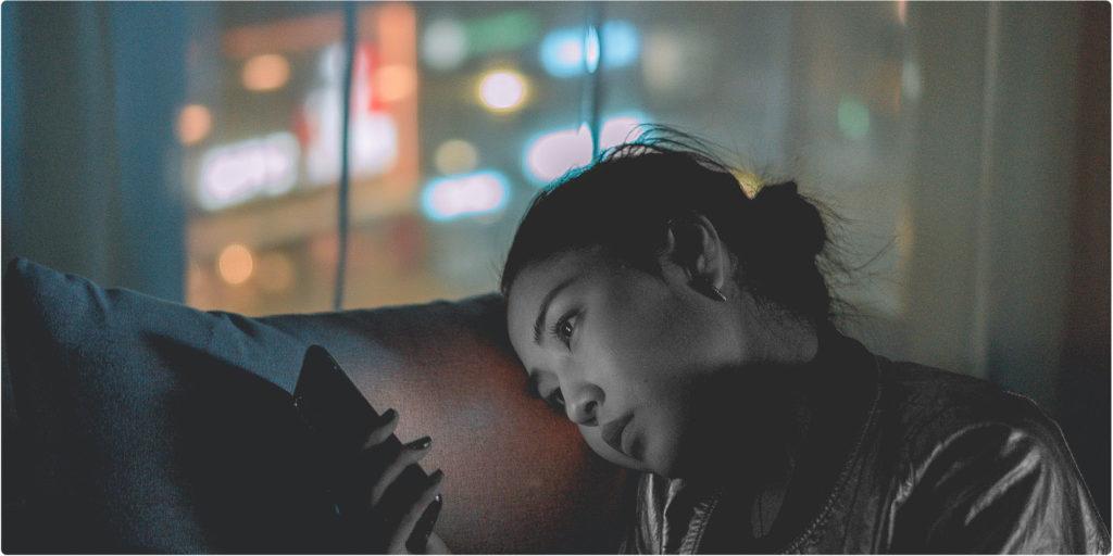 Frau ist allein und schaut auf ihr Smartphone