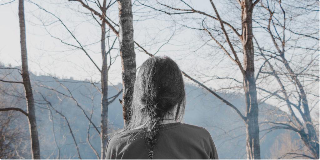 Frau steht alleine im Wald