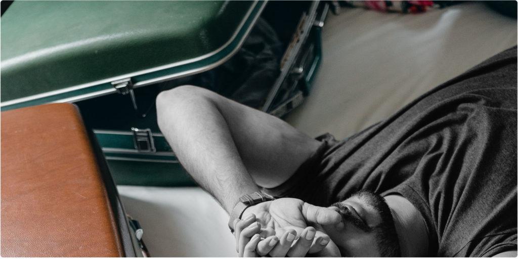 Mann liegt neben einem Koffer