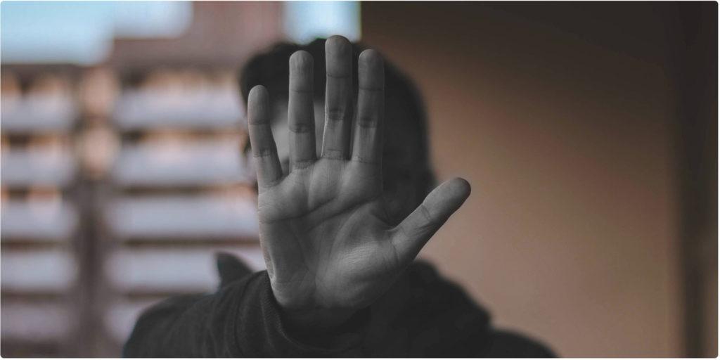 Person streckt die Hand aus und zeigt Stop